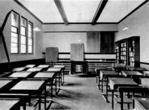 Black and white photo of a traditional classroom with wooden desks